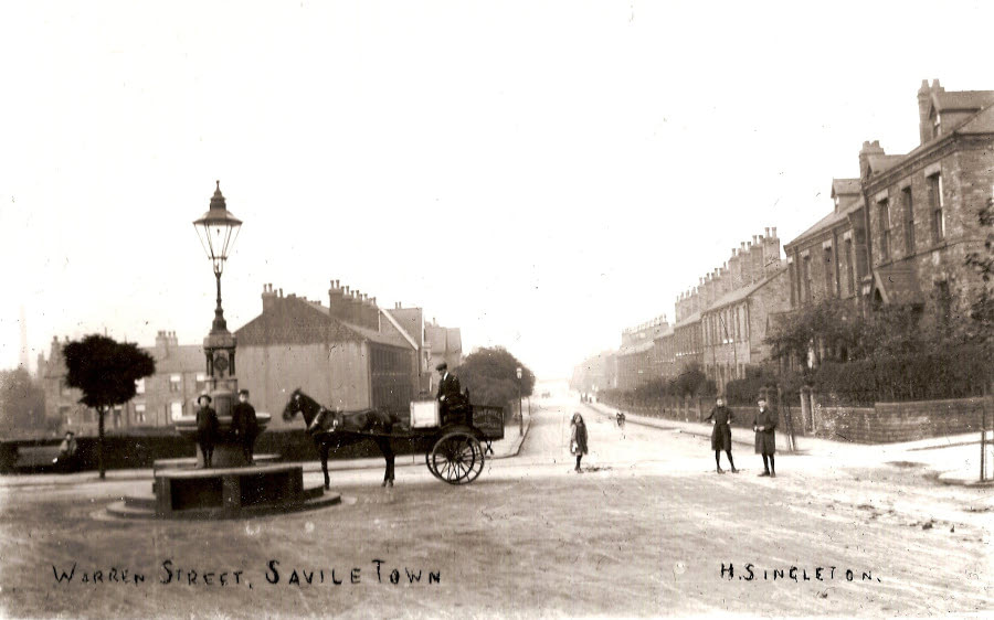 old photo of the drinking fountain with horse drawn carriage
